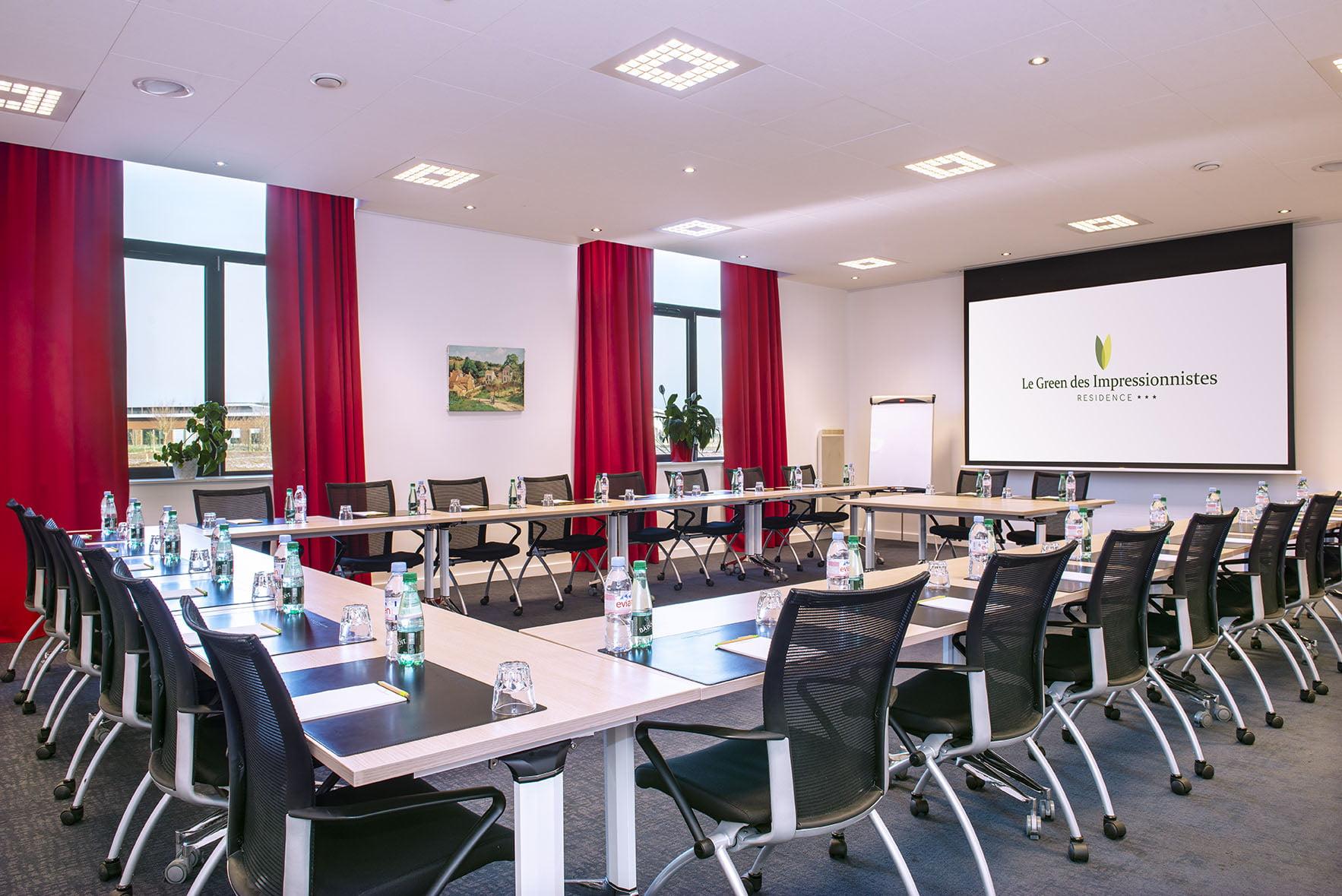 Tables et fauteuils de la salle de séminaire lumineuse du Green des Impressionnistes, avec écran géant