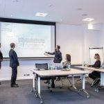 Collègues discutant d'un plan sur l'écran de la salle de séminaire du Green des Impressionnistes