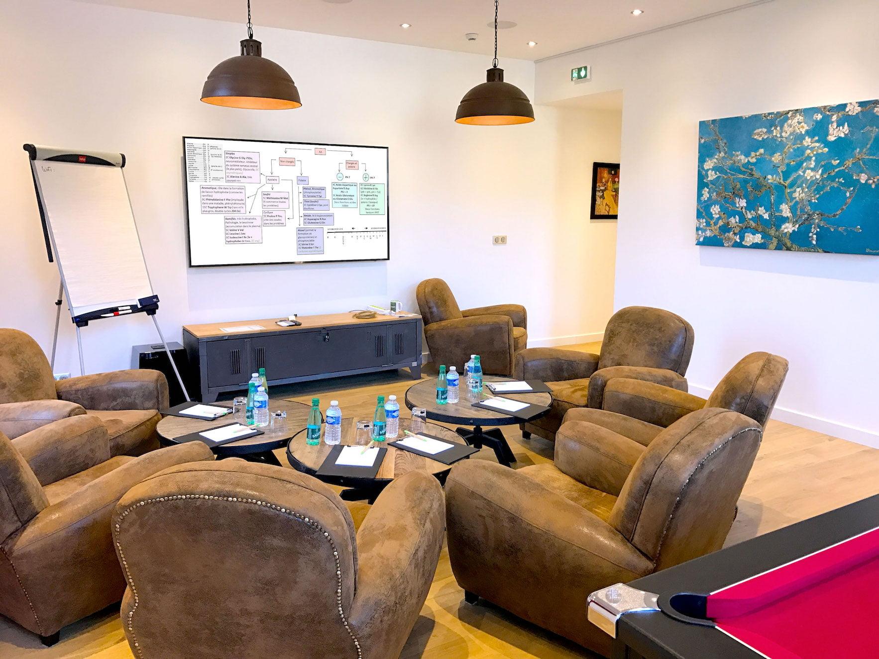 Séminaire au salon du Green des Impressionnistes : fauteuils clubs et tables autour d'un écran géant et d'un paperboard