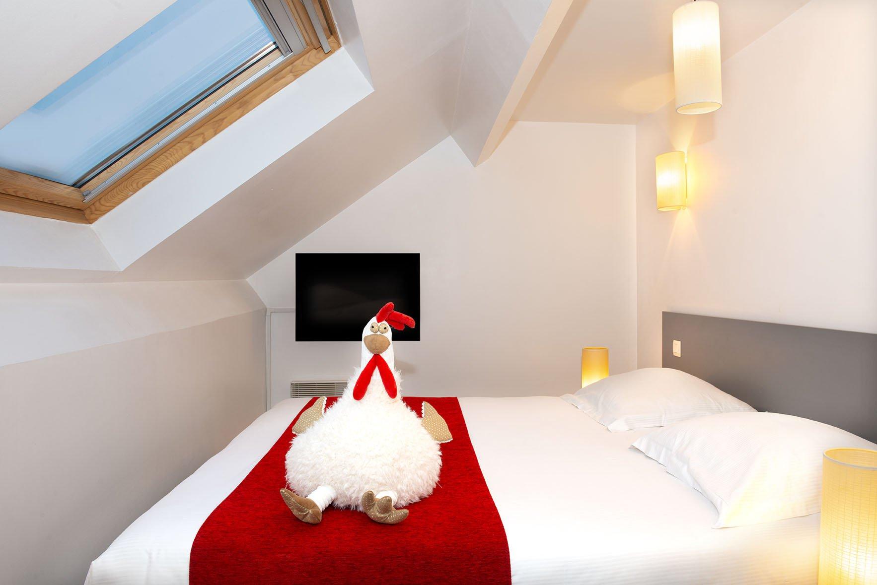 Peluche posée sur un grand lit double d'un appartement familial du Green des Impressionnistes