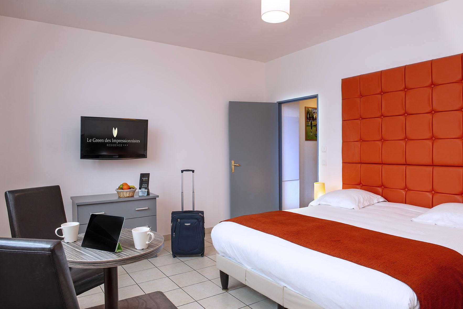 Grand lit double, table, fauteuils et écran dans une chambre du Green des Impressionnistes