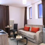 Coin salon d'une chambre du Green des Impressionnistes avec canapé, fauteuils, table, table basse, commode, TV