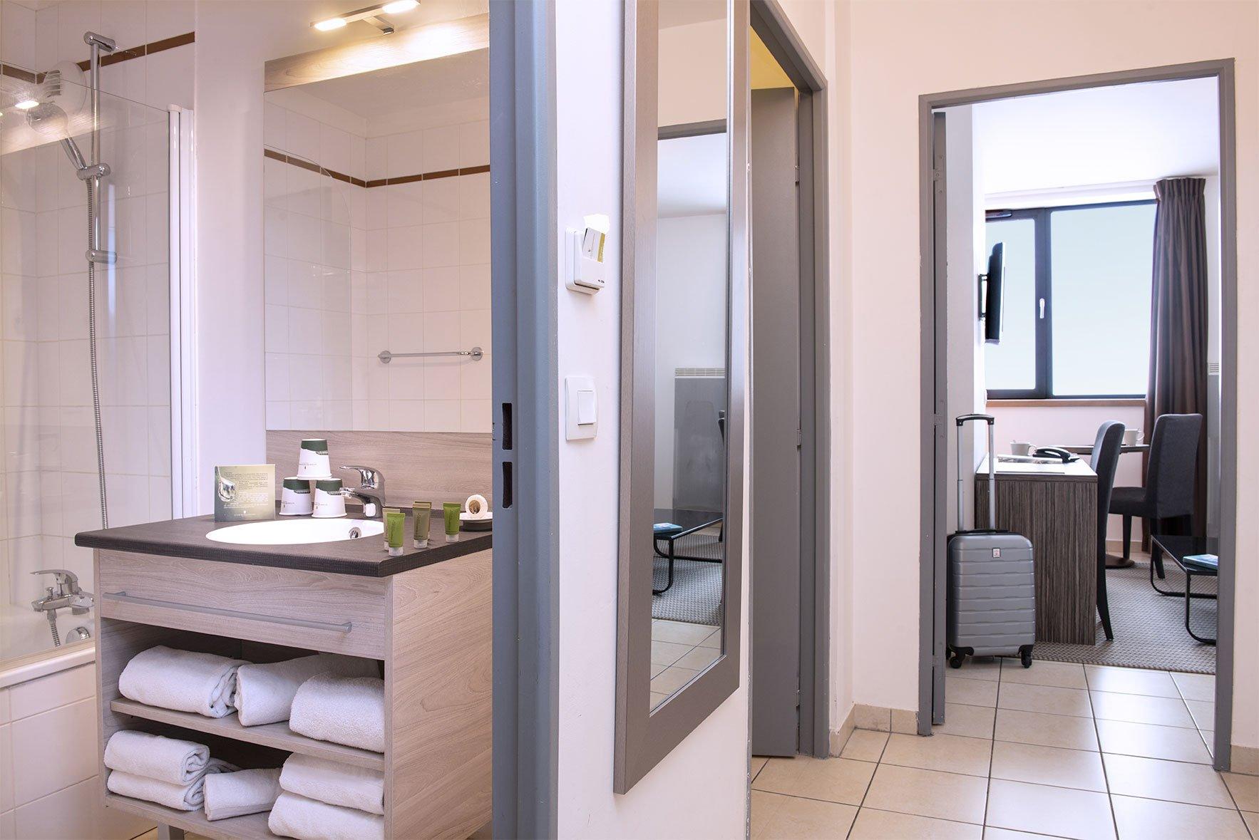 Salle de bain et coin salon d'une chambre du Green des Impressionnistes