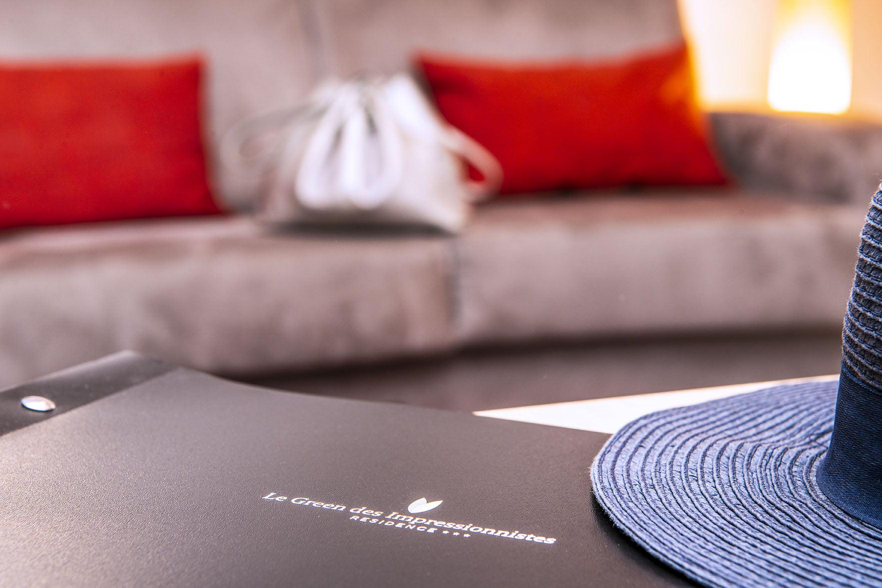 Chapeau et livret d'accueil sur la table d'une chambre du Green des Impressionnistes avec canapé