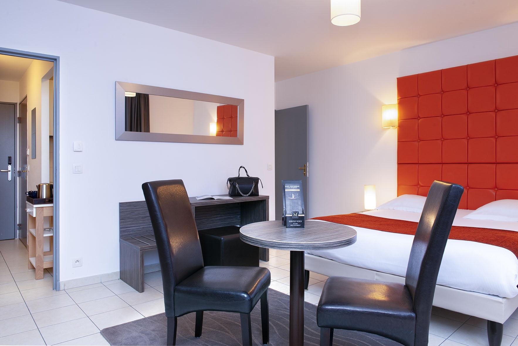 Table, fauteuils et grand lit double au Green des Impressionnistes