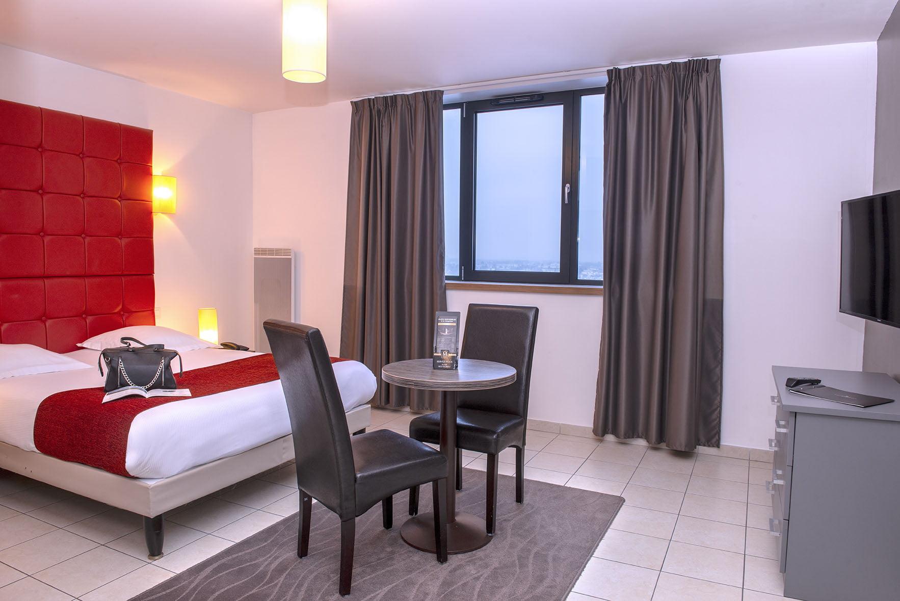 Grand lit double, table ronde et fauteuils devant de grandes fenêtre d'une chambre du Green des Impressionnistes